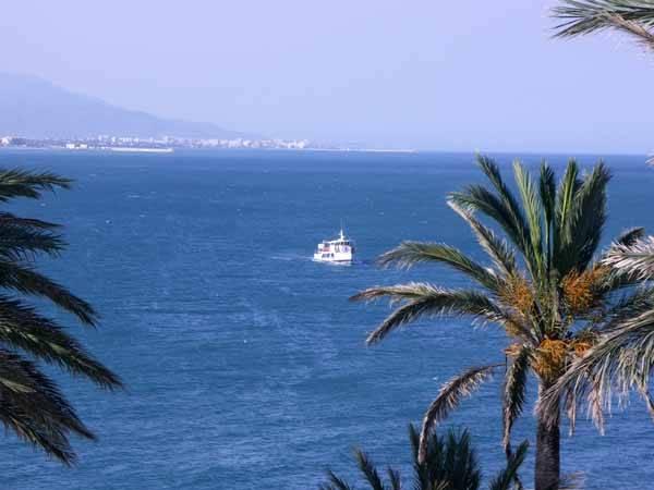 el barco la Golondrina de Peñíscola navegando, al fondo Benicarló y Vinaros