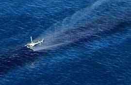 helicóptero derrama spray dispersantes sobre el petróleo