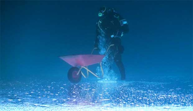 buzo lleva una carretilla al revés bajo el hielo