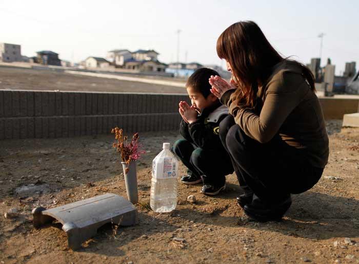 Yuko Sugimoto y su hijo Raito rezan sitio enterrado su perro