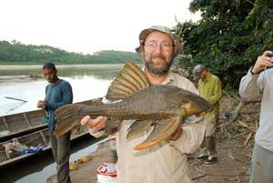 Paulo Petry con un pez gato comedor de madera