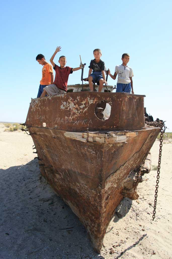 niños jugando en un barco oxidado en el desierto de Mo'ynaq