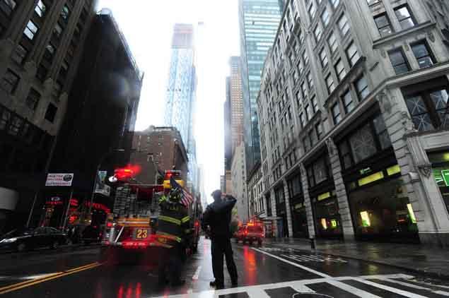 bomberos vigilan la grúa rota en Nueva York