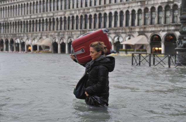 turista con maleta al hombro en una Venecia inundada