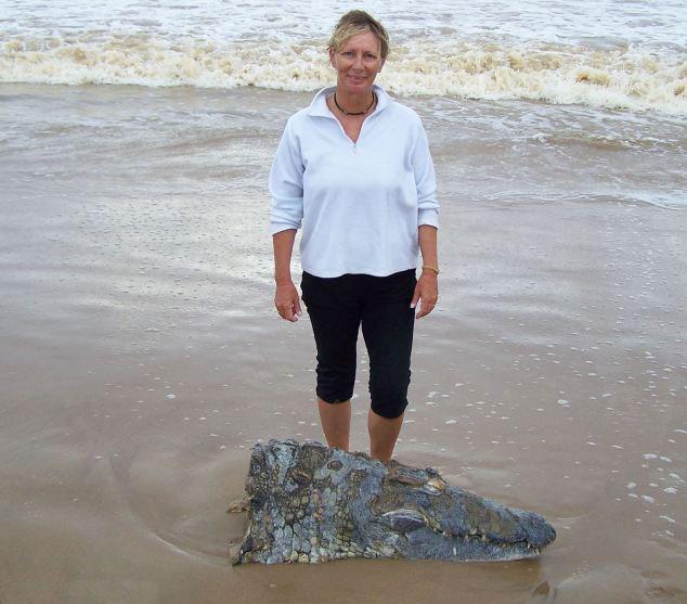 Neale junto a la cabeza de cocodrilo en una playa de Sudáfrica