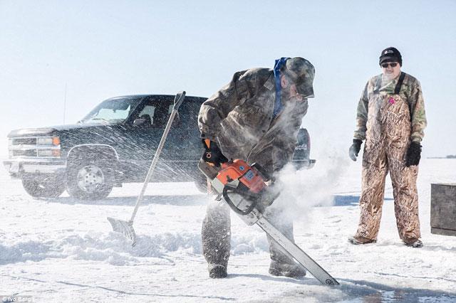 pesca de esturión en un lago helado - motosierra