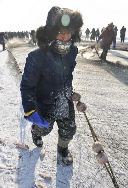 pescador abrigado para pescar bajo el hielo en China