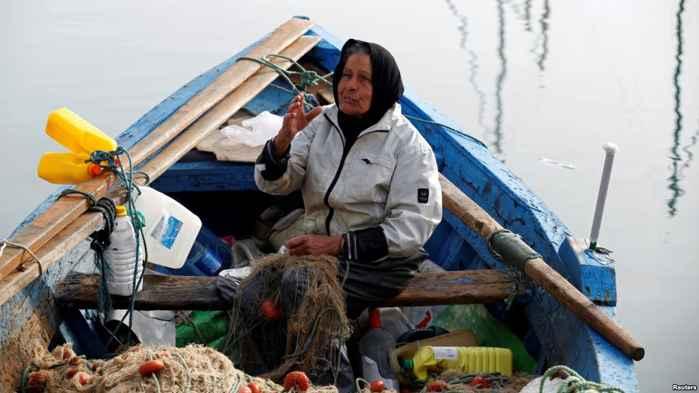 mujer repara una red después de pescar
