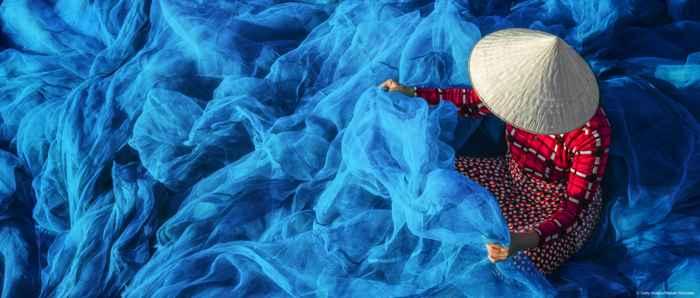 mujer cosiendo una red de pesca