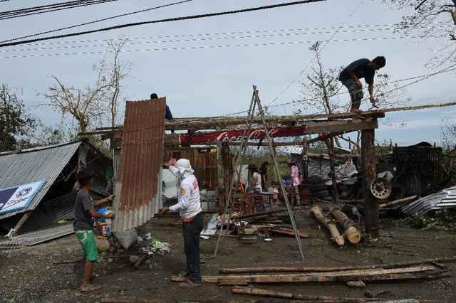 familia reconstruye una casa tras el tifón Haima en Filipinas