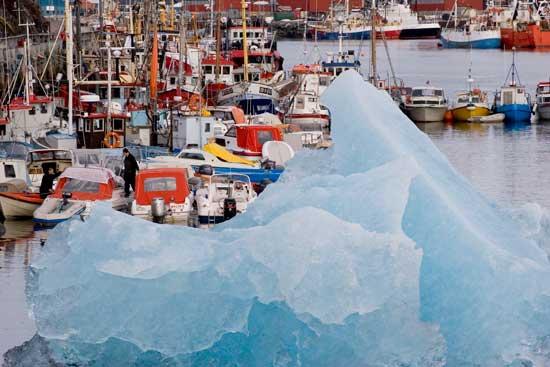 barcos junto a un iceberg en el puerto de Lulissat