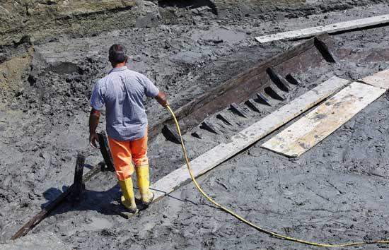 echando agua a los restos del barco antiguo romano