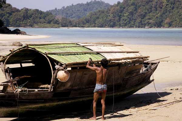 reparando el techo de un barco moken en la playa