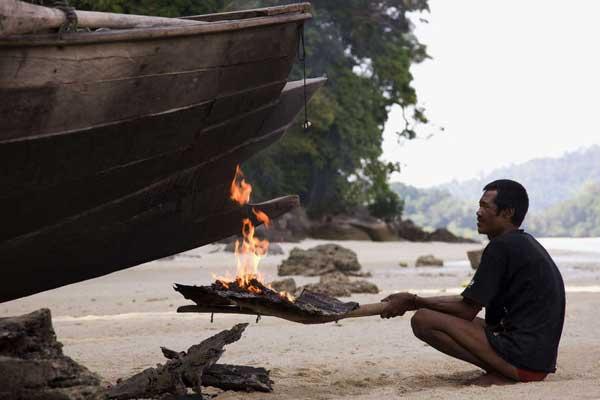 quemando la quilla de un Kabang con algas