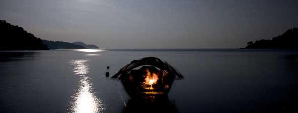 una familia moken cena en su barco bajo una luna llena