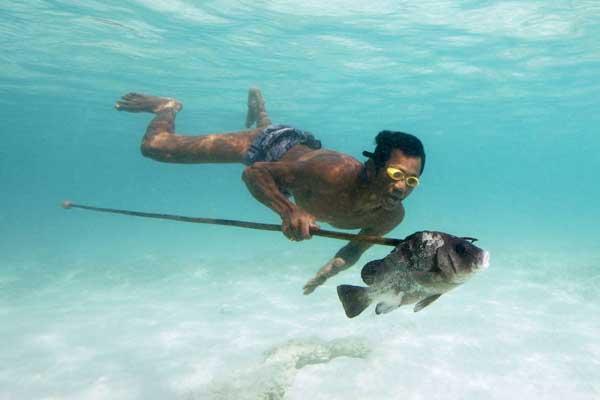 un moken pesca buceando