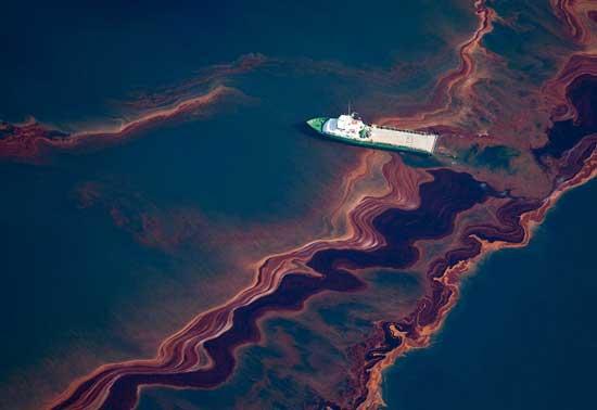 barco navega a través de la mancha de petróleo