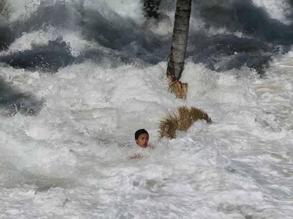 Una gran ola del tsunami del 2004 arrastra a una persona