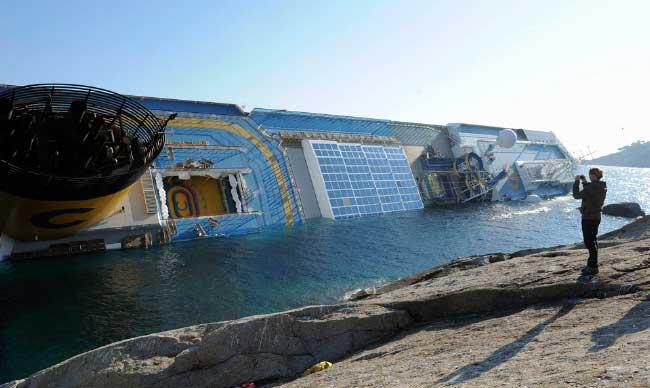 una mujer toma una foto del Costa Concordia